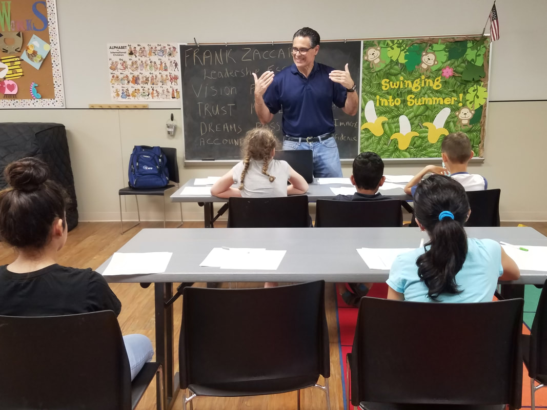Frank Zaccardo in front of a group of boys and girls learning about leadership